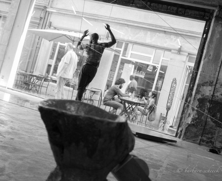 homme qui danse devant une vitrine qui donne sur une rue